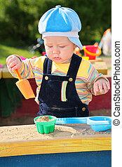 little boy plays in sandbox