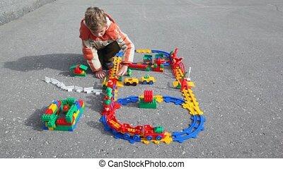 boy plays plastic railway