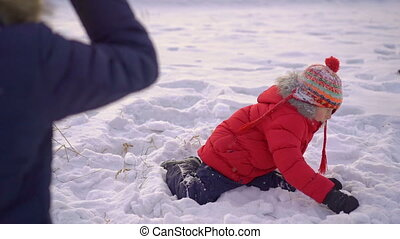 Little boy plays snowballs with his mother. Slowmotion shot