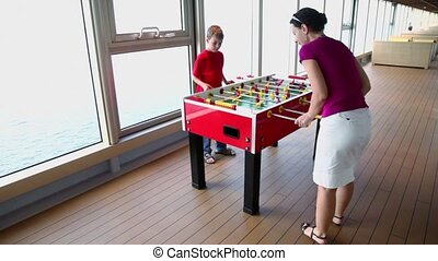 Little boy plays table football with his mother and waves of sea water are in window behind
