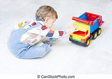 Little boy plays with a car and spinning top toy
