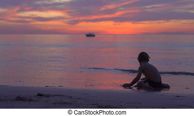 little boy plays with a sand during the beautiful sunset on...