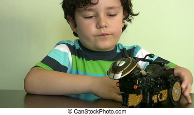 Little boy plays with his  toy moto