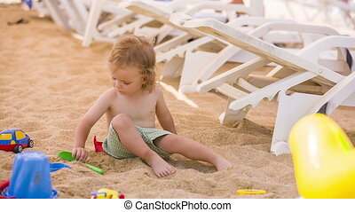 Little Boy Plays With Toys In Sand
