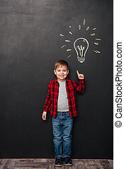 Little boy pointing up and having idea over chalkboard background