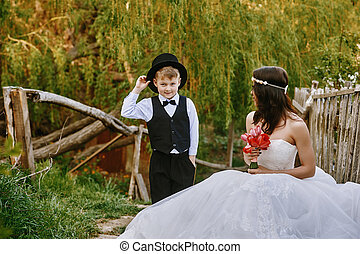 Little boy posing in the cylinder next to the bride . Wedding day