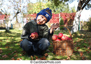 little boy posing outdoors with apples