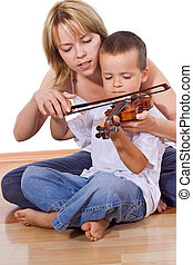 Little boy practicing the violin sitting on the floor with a...