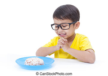 Little boy praying before eating