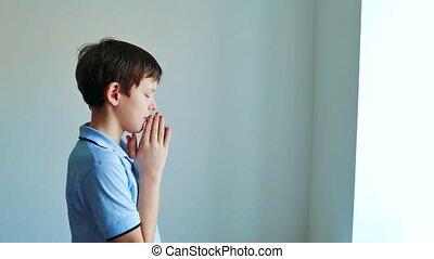 Little boy praying child praying indoors black background....