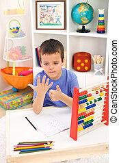 Little boy preparing for elementary school doing simple math...