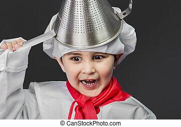 Little boy preparing healthy food on kitchen over grey background, cook hat