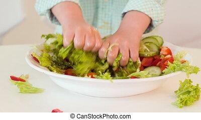 Little boy preparing salad