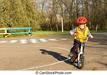 Little boy dressed in safety gear preparing to ride his bicycle standing astride with his foot on the pedal on a quiet country road