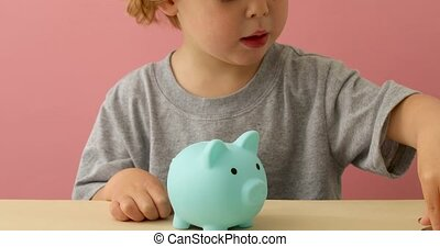 Little boy putting coins in a piggy bank at home