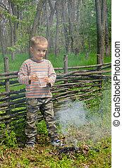 Little boy putting out a camp fire