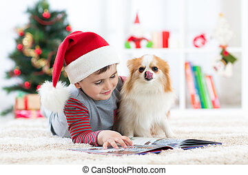 Little boy reading a book and dog at Christmas