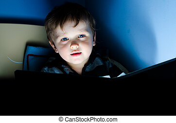 Little boy reading a book in his bed at night