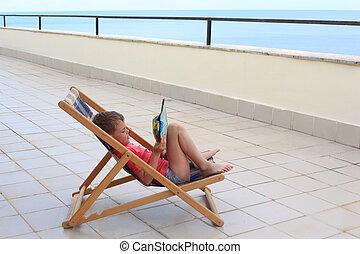 little boy reads in lounge on veranda