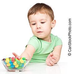 Little boy refusing to eat candies
