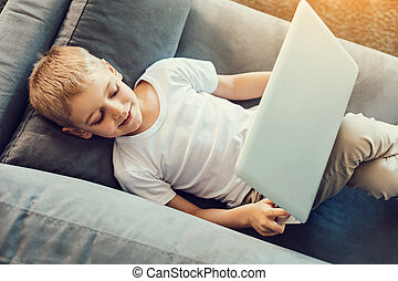 Little boy relaxing with a laptop