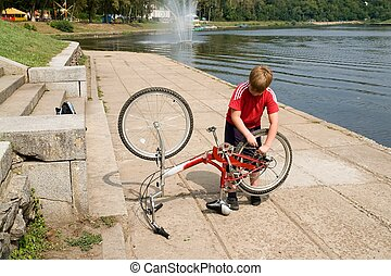 boy repairs the bicycle
