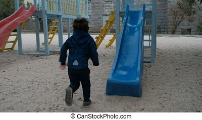 Little boy rides down a plastic slide on the playground in cool day.