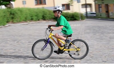 Little boy rides on bike. Summer time in the town.