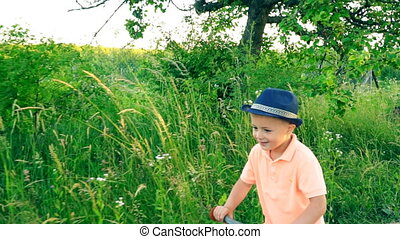 little boy riding a bicycle without pedals on the nature