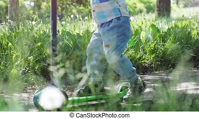 Little boy riding mini scooter, kick scooter in the park on sunny summer day in slow motion. 1920x1080