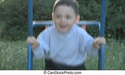 little boy riding on a swing 1