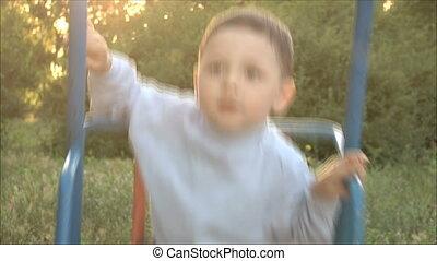 little boy riding on a swing 2