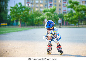 Little boy riding on rollers in the summer in the Park. Happy child in helmet learning to skate