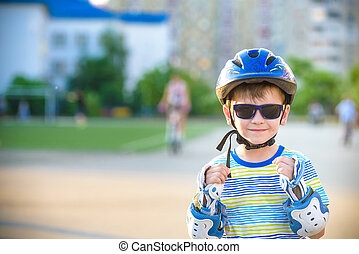 Little boy riding on rollers in the summer in the Park. Happy child in helmet learning to skate. Safety in sport