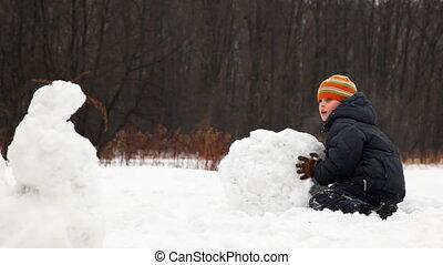 little boy rolls big snow ball for snowman