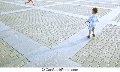 Little boy running around the squares of summer
