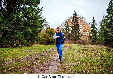 Little boy running in autumn forest. Healthy lifestyle