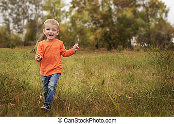 Little boy running in colorful autumn park, copyspace