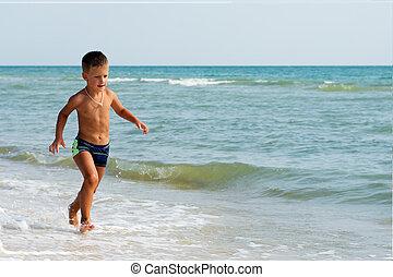 Little boy running in summer at sea beach