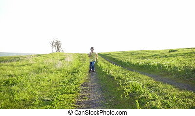 Little boy running on rural road in green grass field