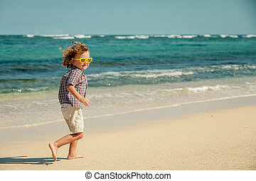 little boy running on the beach at the day time