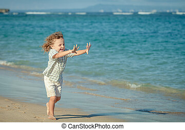 little boy running on the beach in the day time