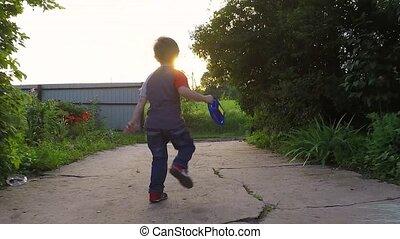 Little boy running outside. sunset
