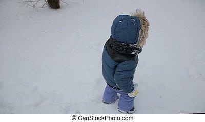 Little boy running through the snow slow motion
