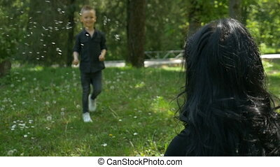 Little boy running to embrace mother being happy and smiling in nature