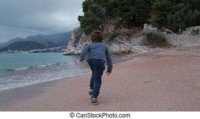 Little boy runs fast alone along sandy seacoast of bay.