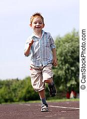 little boy runs in a summer park