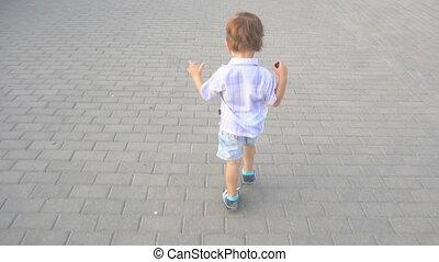 little boy runs on the road