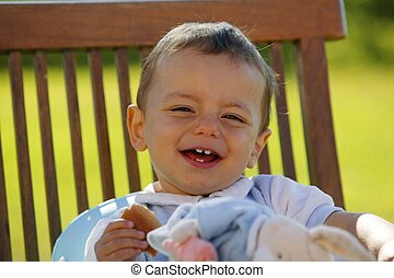 Little boy sat eating in the garden