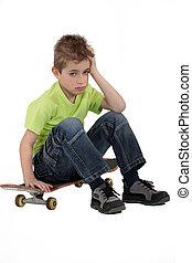 Little boy sat on skateboard